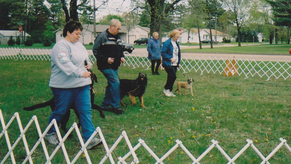 Club members practice Team Obedience - Lori Whitney and her Labrador Retriever, Roger LaBarge and his Belgian Tervuren, and Kathy Schuh and her Border Terrier. Coaching in the background is Shirley LaBarge.